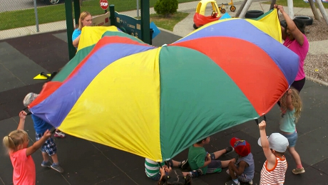 Children and caregivers playing with a multicoloured parachute outside at a day care facility.