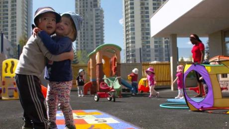 Deux enfants enlacés sourient sur un jeu de marelle dans l'aire de jeu d'une garderie.