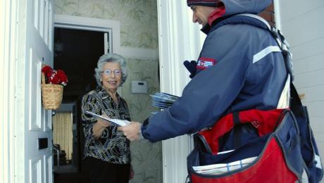 Facteur livrant du courrier au domicile d'une femme toute souriante