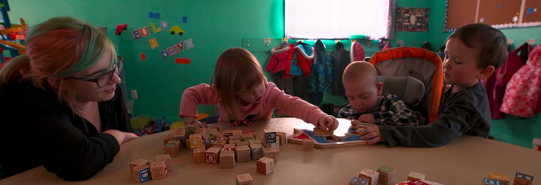 Des enfants jouent autour d'une table avec des cubes sous le regard attentif d'une éducatrice.