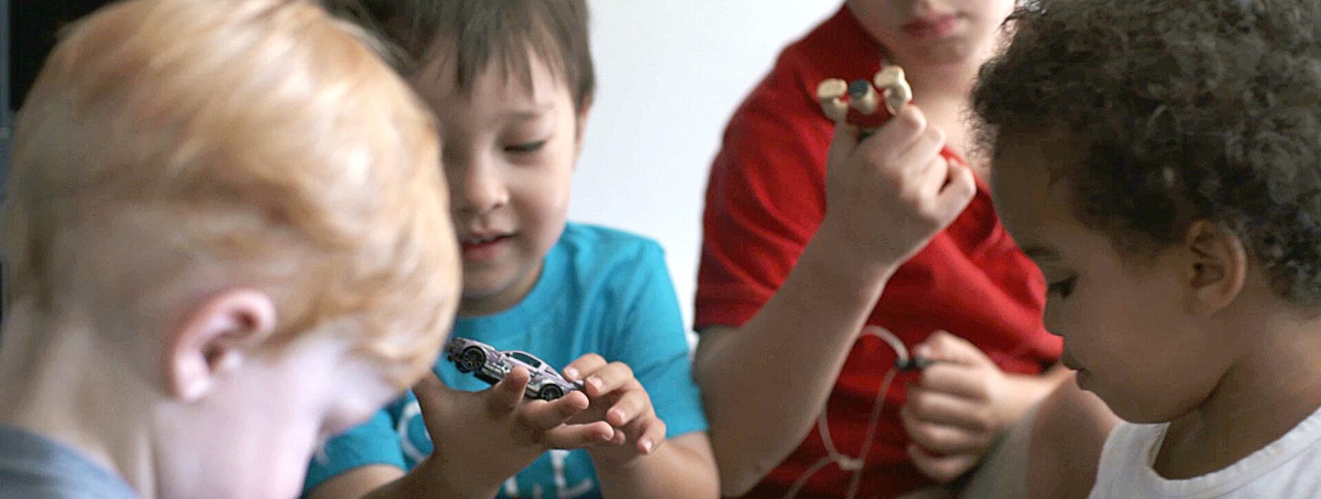Un enfant joue avec une petite voiture au milieu d'autres enfants.
