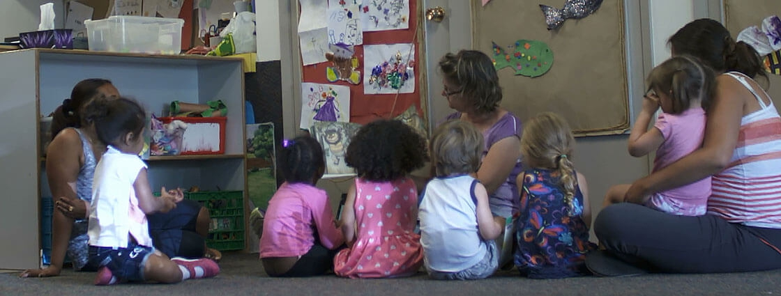 Children and care givers sit on a carpet and read a book for story time.