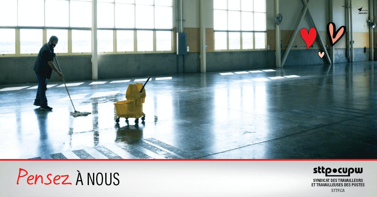 Photo d'une personne qui lave le plancher d'un entrepôt vide.